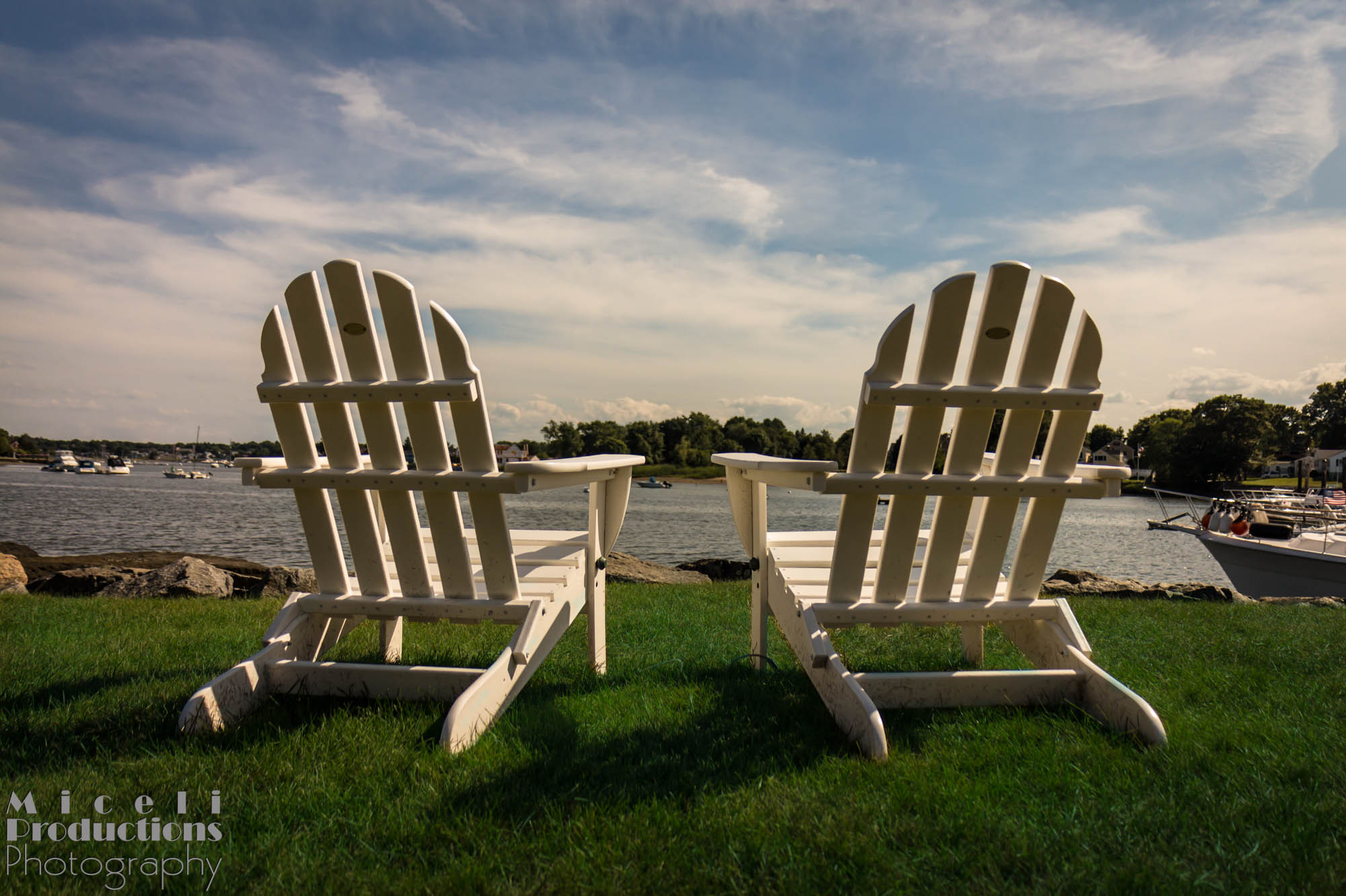 Two adirondack chairs over looking a smooth harrbor of water. © Miceli Productions Photography