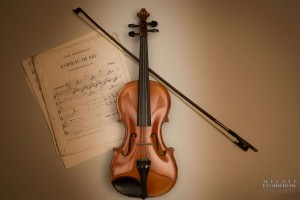 Violin with bow and sheet music on a tan background.