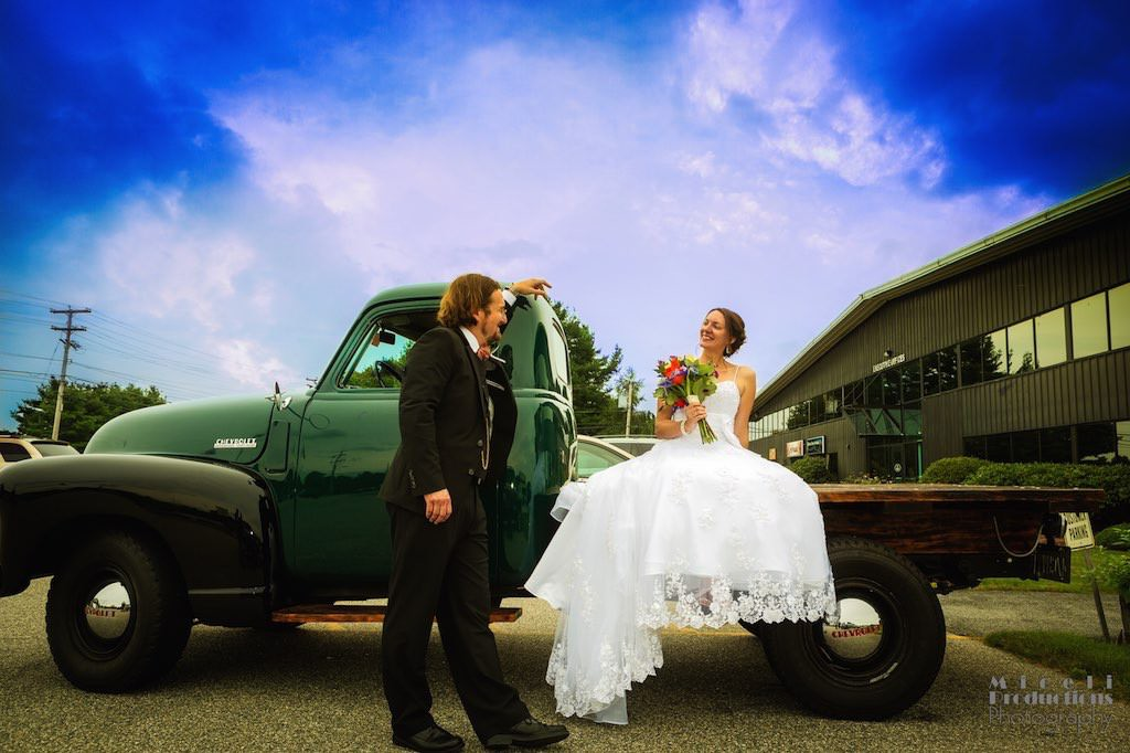 Bride and groom couple share a moment sitting on an old Chevy pick-up truck with a bright blue sky on their wedding day.