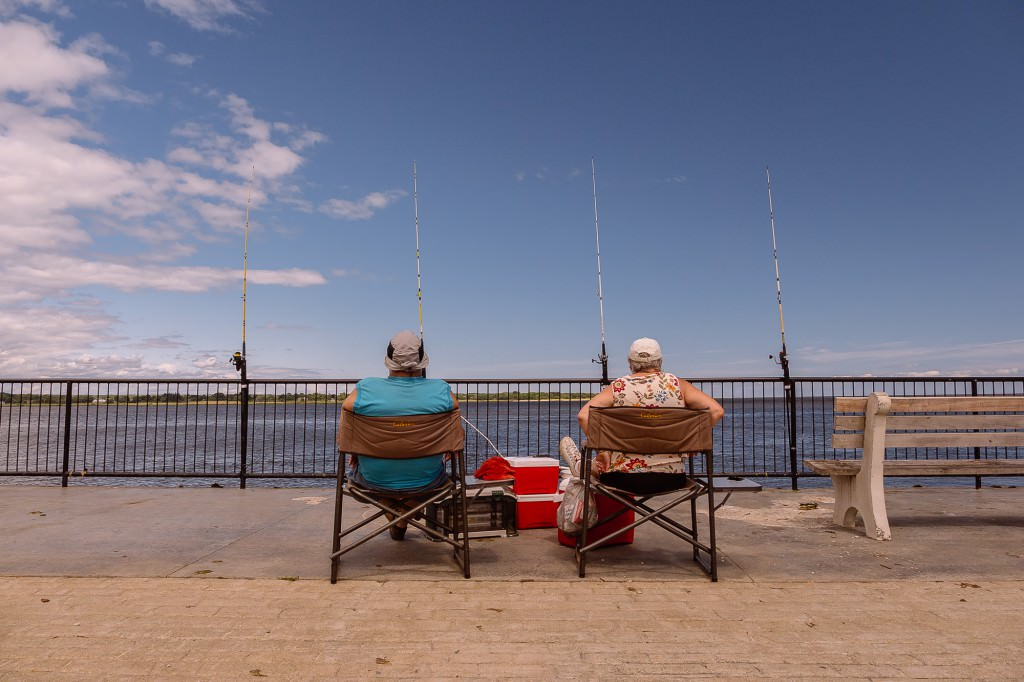 A retired couple being fishermen sit on the pier in Old Saybrook, Connecticut on shoreline CT during a beautiful day.