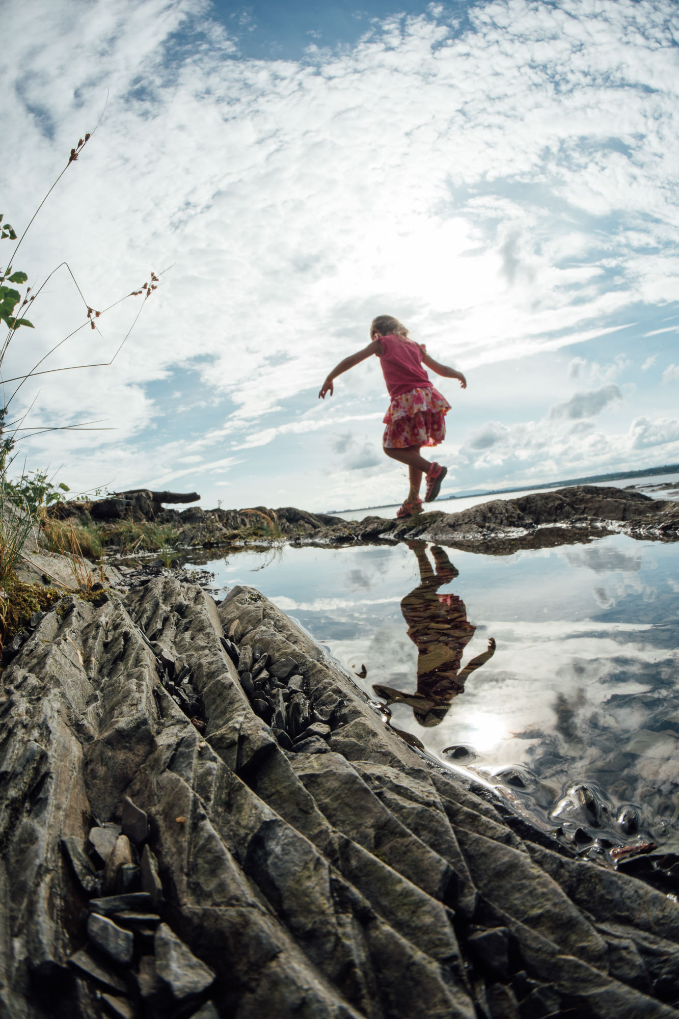 Young girl runs through the tide pools near the beach with the open blue sky above her.