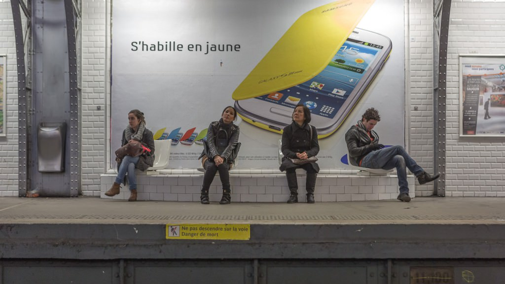 Four individuals sit in a Paris train station waiting for the subway train. They are all evenly spaced, doing their own activities.