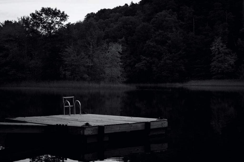 A photo tribute to Creepshow 2, The Raft, by Stephen King. A black and white photo of a dock with a ladder in the middle of a lake.