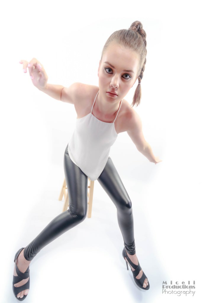 Girl model with a white tank top and black pleather pants walking strangely towards camera, looking like a doll with an effect that makes her head seem larger than her body.