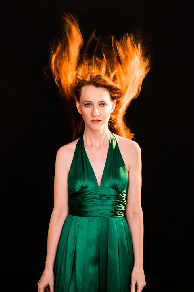 Woman with shocking red hair in a green dress in the same pose as Drew Barrymore in Firestarter.