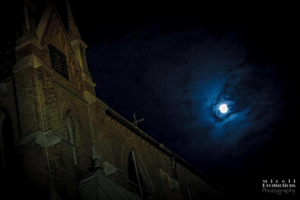 Supermoon illuminates church in Waterbury, CT. Gothic looking cathedral on the left with the moon in the cloud to the right of the image.