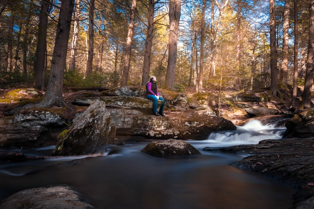 Woman hiker sits on a rock overlooking an evergreen forest stream, Mad River, in Connecticut. Part of the Blue-Blazed Hiking Trail System.