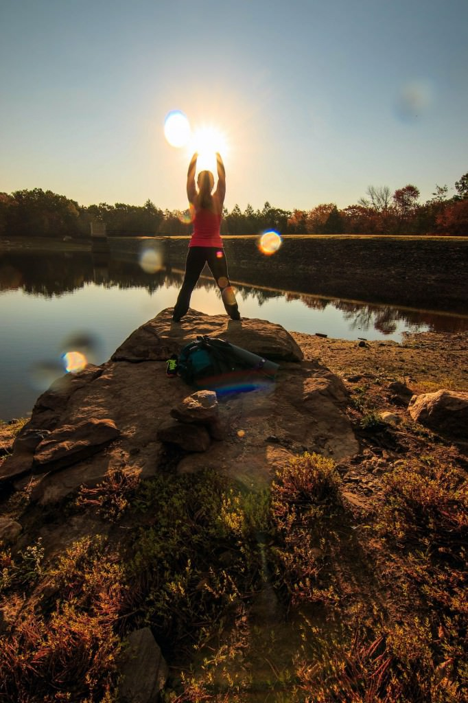 Photo of early morning sunrise with girl holding the sun in her up stretched hands while standing on a rock outcropping near a lake.