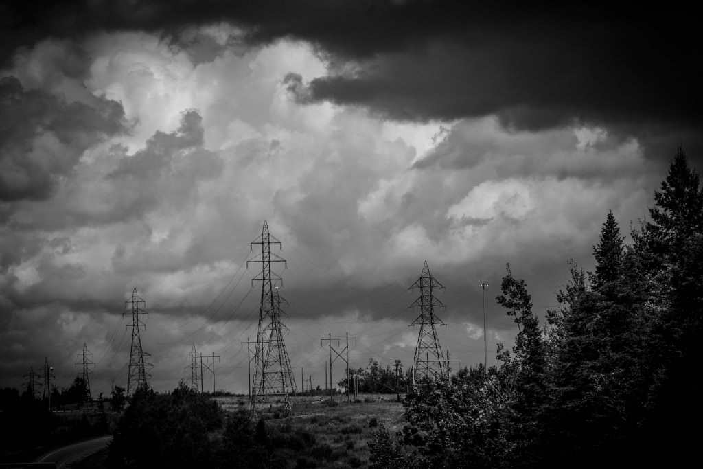 High tension electrical grid towers that span a valley with looming clouds overhead.