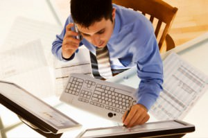 Photo of a man on the phone at a keyboard at his desk. Image from iStockPhoto