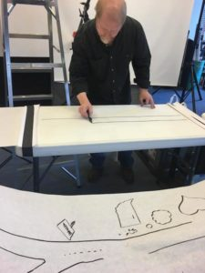 Behind the scenes, artist draws an image for a whiteboard product video.